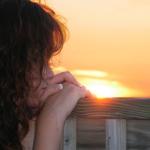 Vrouw kijkt in gedachten verzonken naar opgaande of ondergaande zon